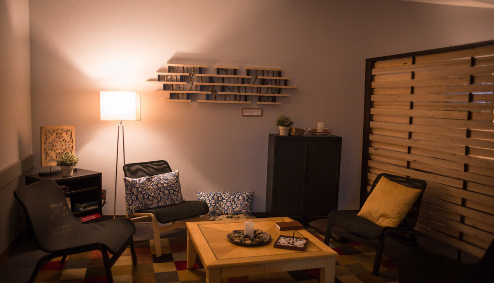 A cozy prayer room with dim lighting and comfy furniture.