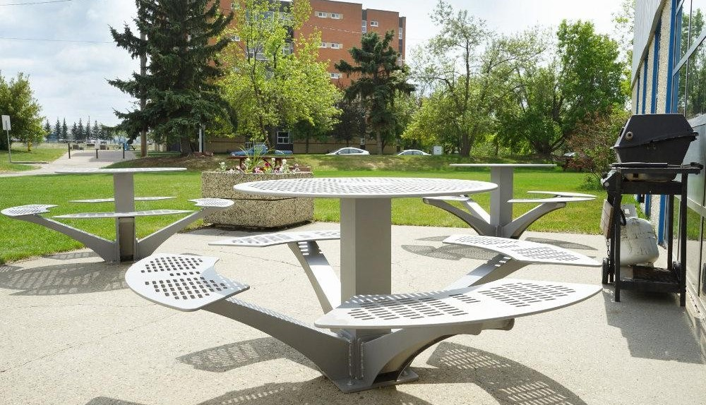 Round picnic tables on paved area outside of King's.