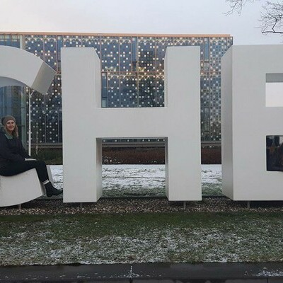 Large letters C, H, and E with students sitting on them.