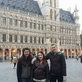 Three female students stand in the Grand-Place in Brussels