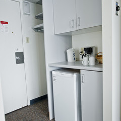 Residence room showing cabinets, counter, closet and mini fridge space.