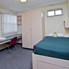 Individual room with bed and storage, large wardrobe and desk.