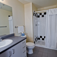 Apartment bathroom with large shower. toilet and vanity area.