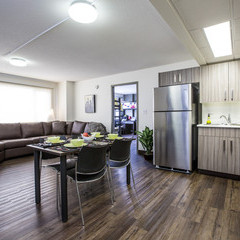 Kitchen/ living room area of suites in residence with large leather sectional, fridge and counter space, kitchen table.