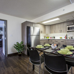 Kitchen space in suites residence with table, fridge, sink, counter and cupboard space, stove top and convection oven.