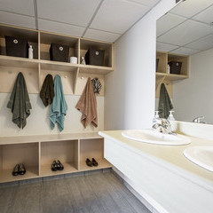 Storage and towel hanging space adjacent to the vanity area with a double sink in the suite rooms.