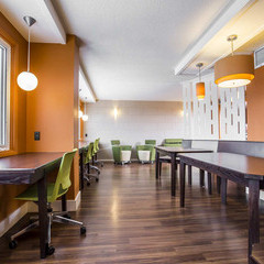 Floor 7 lounge in the tower residence at King's with bright orange walls and natural lighting. Large table work spaces and individual work spaces with bright green chairs.