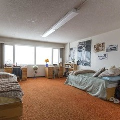 Residence room with two beds and orange shag carpet.