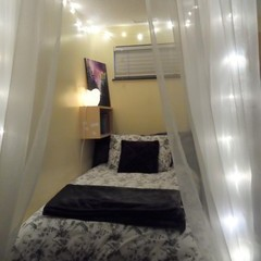 Bed set up with drapery and lights hanging over top in apartment bedroom.