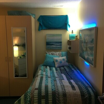 Apartment bed with blue quilt and blue decorative accents