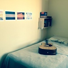 Apartment room bed with guitar laying on it.