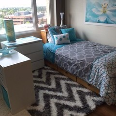 Blue and grey bedding, grey and white chevron carpet and white accent furniture decorate a residence room.