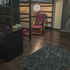 Chair and footstool set up underneath loft bed with lamp hanging from bed.
