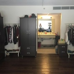 Wardrobe area with open clothing racks and opening to vanity area of bathroom.