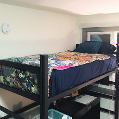Top of loft bed showing blue and floral bedspread.