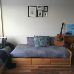 Bed set up like a couch with pillows and guitar resting on top, pictures hung in gallery format on wall.