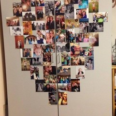 Pictures hung in a heart shape on the doors of a wardrobe.