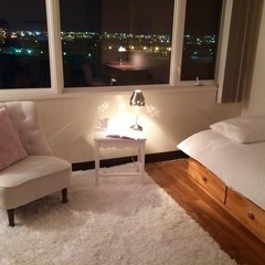 White chair with pink throw pillow on white shag throw rug beside bed.