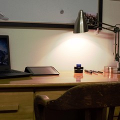 Close up of desk set up with lamp and laptop.