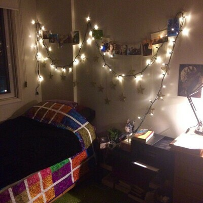 Fairy lights hung above bed with pictures.