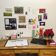 Desk space with laptop, open planner and pictures and notes hanging on the wall.