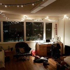 Residence room set up with lights hung above window, comfy chair and desk in front of window.