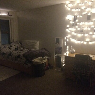 Cozy residence room with fairy lights hung and pictures hanging off them,
