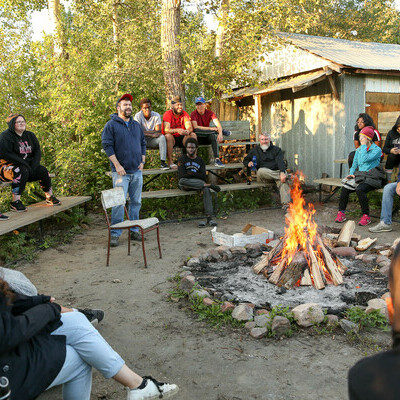 The Residence Coordinator and students around a campfire.