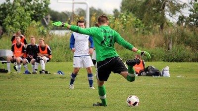 Soccer goalie kicking the ball during a game.