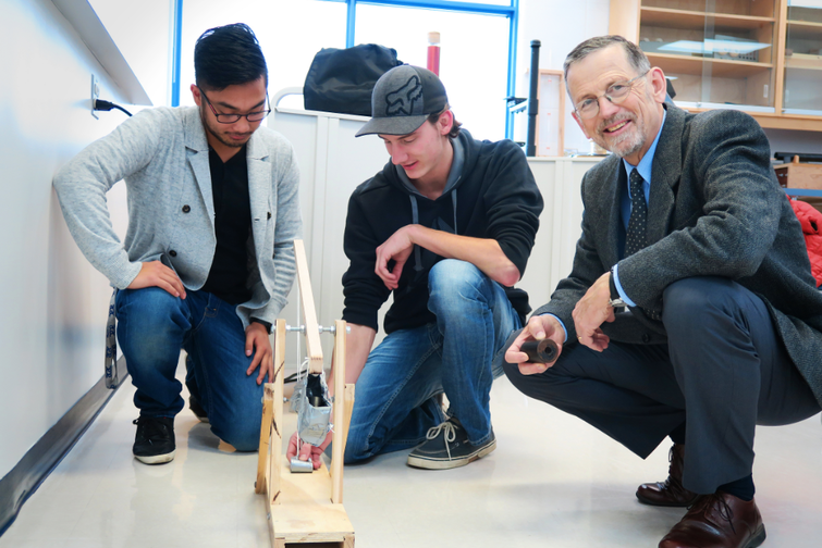 Physics and astronomy professor emeritus Dr Brian Martin building a model trebuchet with students.