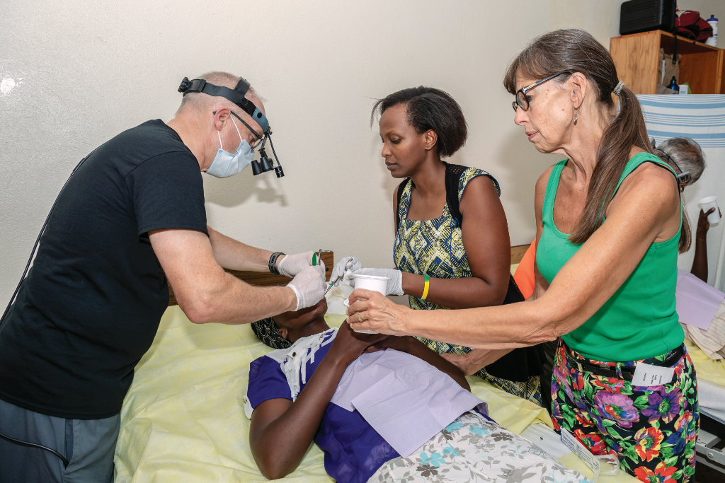 On another one of his service trips to Rwanda, Dr. Wiebe works closely with local medical professionals like Isabelle (centre) to perform complicated dental procedures such as oral tumour extractions. Photo credit: Rob Hislop