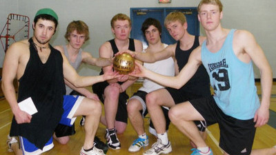 Group of men in the gym holding their dodge ball winning trophy.