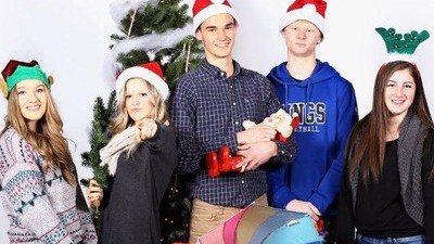 Students with Christmas hats and props posed at a photobooth.