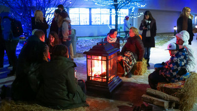 Students huddled around a fire in front of Christmas lit trees at King's.