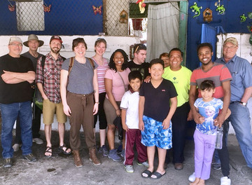 deKoning (third from the left) with the Quest group, Justino (a third-generation resident of an urban squatter settlement), and his family. Residents are regularly threatened with jail time or expulsion from their homes as a result of not having ownership