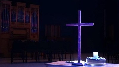 Lent setup in Knoppers Hall with cross in forefront and organ in back.