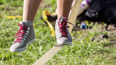 Student stepping on a slack line.
