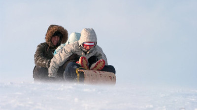 Students tobogganing down a hill in parkas.