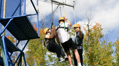 Three students with helmets harnessed into a swing.