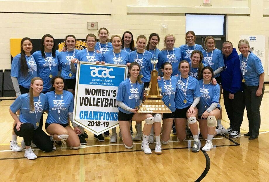Eagles women's volleyball team with their championship banner